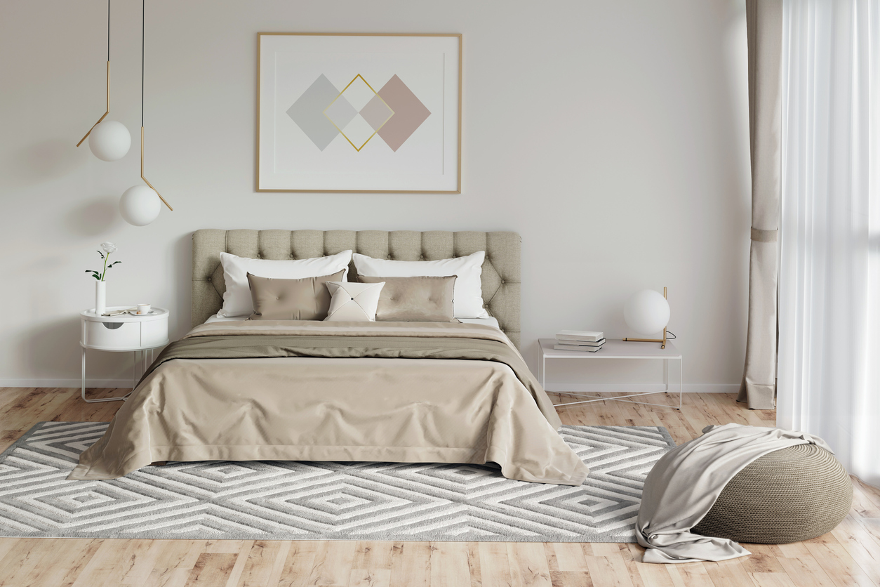 Cozy bedroom in warm colors with painting, a nightstand, a pouf, and a plaid. Front view